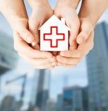 Hände, die Papierhaus mit rotem Kreuz halten Lizenzfreie Stockbilder