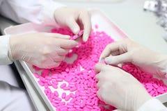 Hände, die Pillen - Qualitätskontrolle anhalten Stockfotografie