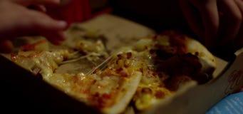 Hände, die Pizzascheibe ergreifen stock footage