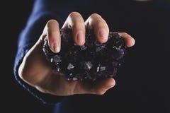 Hände, die purpurroten Amethyst Kristall halten lizenzfreie stockfotos
