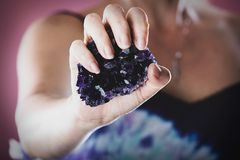 Hände, die purpurroten Amethyst Kristall halten lizenzfreie stockbilder