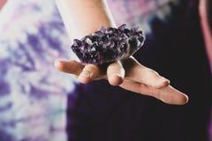 Hände, die purpurroten Amethyst Kristall halten stockfoto