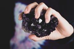 Hände, die purpurroten Amethyst Kristall halten stockbild