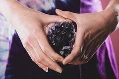Hände, die purpurroten Amethyst Kristall halten stockfotos