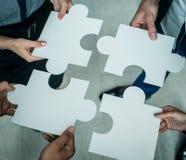 Hände, die Puzzlespiel anhalten Lizenzfreie Stockfotos