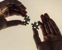 Hände, die Puzzlespiel anhalten Lizenzfreies Stockbild