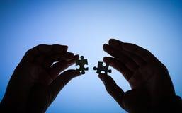 Hände, die Puzzlespiel anhalten Stockfotos