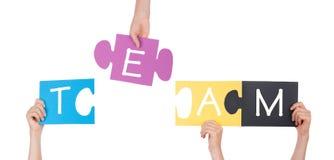 Hände, die Puzzlespiel mit Team halten Lizenzfreies Stockfoto