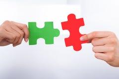 Hände, die Puzzlespielstücken sich anschließen Stockfoto