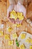 Hände, die Ravioliteigwaren auf Tabelle halten Stockfotografie