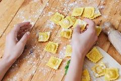 Hände, die Ravioliteigwaren auf Tabelle halten Stockbild