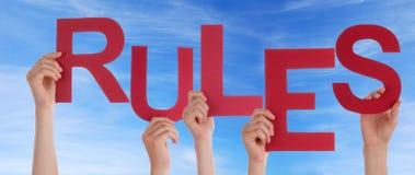 Hände, die Regeln im Himmel halten Stockfotos