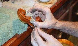Hände, die Rohrschelle auf Violinenrolle setzen Lizenzfreies Stockbild