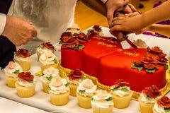 Hände, die rote Samt-Hochzeitstorte schneiden Stockfotos