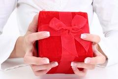 Hände, die roten Samt-Geschenk-Kasten anhalten Stockfoto
