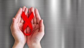 Hände, die rotes Band auf Metallhintergrund für Welt-Aids-Tag halten Stockbild