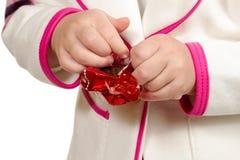 Hände, die Süßigkeit auspacken stockbilder