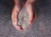 Hände, die Sand anhalten Stockbild