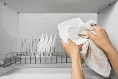 Hände, die saubere Platte mit Tuch abwischen Stockfoto