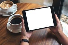 Hände, die schwarzen Tabletten-PC mit weißem leerem Bildschirm und Kaffeetassen auf Tabelle halten Lizenzfreies Stockbild