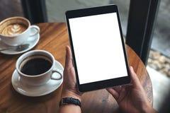 Hände, die schwarzen Tabletten-PC mit weißem leerem Bildschirm und Kaffeetassen auf Tabelle halten Lizenzfreie Stockfotos