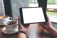 Hände, die schwarzen Tabletten-PC mit weißem leerem Bildschirm und Kaffeetassen auf Tabelle halten Stockbild