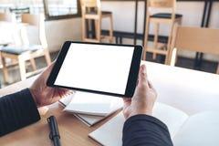 Hände, die schwarzen Tabletten-PC mit weißem Tischplattenschirm des freien Raumes beim Arbeiten an Notizbüchern im Büro halten un lizenzfreie stockfotos
