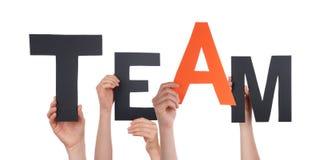Hände, die schwarzes orange Team halten Stockfotos