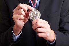 Hände, die Silbermedaille anhalten Stockfotos