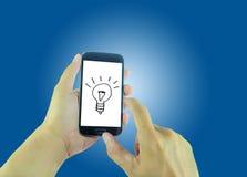 Hände, die Smartphone auf dem Schirm mit Glühlampen halten Stockbilder