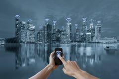 Hände, die Smartphone und Stadtbild wifi Netzkonzept halten Lizenzfreies Stockfoto