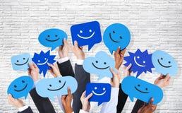 Hände, die Smiley Faces Icons halten Stockfoto