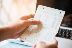 Hände, die Sparkontosparbuch, Buchbank-Laptop backgro halten Stockfoto
