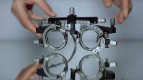 Hände, die spezielle Gläser für Visionskontrolle, Diagnose von Augenkrankheiten setzen stock video footage