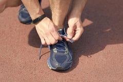 Hände, die Spitzee auf Turnschuh, Rollbahnhintergrund binden Hände des Sportlers mit dem Pedometer, das an Spitzee bindet stockfotos