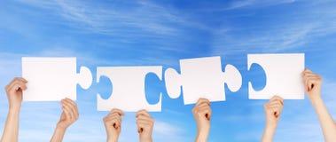 Hände, die Stücke eines Puzzlespiels mit Kopienraum halten lizenzfreie stockbilder