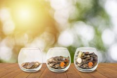 Hände, die Stapel der Münzen schützen Münzen im Glasglas Investitionsgeld conce Stockfotografie