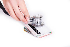 Hände, die Stethoskop auf Kreditkarten als Symbol des Geldautos halten Lizenzfreie Stockbilder