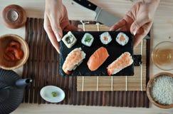 Hände, die Sushi kochen Lizenzfreie Stockbilder