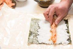 Hände, die Sushi mit Lachsen und nori kochen Lizenzfreies Stockbild