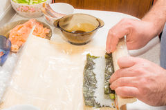 Hände, die Sushi mit Reis, Lachsen und nori kochen Stockbild