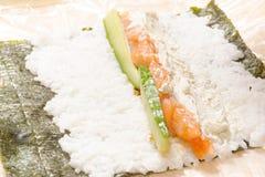 Hände, die Sushi mit Reis, Lachsen und nori kochen Stockfoto