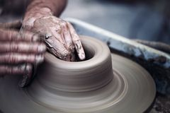 Hände, die an Töpferscheibe, künstlerisches getont arbeiten Stockfotos