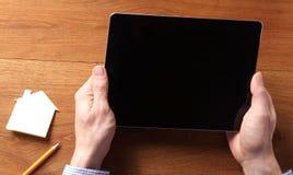 Hände, die Tablet-Computer am Holztisch halten lizenzfreie stockbilder