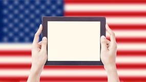 Hände, die Tablette auf unscharfer USA-Flagge mit Beschneidungspfad insi halten Lizenzfreies Stockfoto