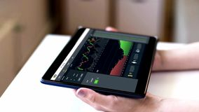 Hände, die Tabletten-PC mit Diagrammen auf Schirm halten stock video