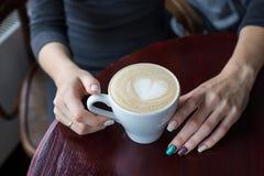 Hände, die Tasse Kaffee mit Schaum und Herzen halten Lizenzfreie Stockfotografie