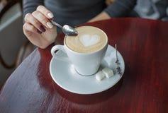 Hände, die Teelöffel über Tasse Kaffee mit Schaum halten Stockbild
