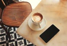 Hände, die Telefon für simsende Mitteilung halten Stockfotos