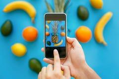 Hände, die Telefon halten und Foto von Ananas in der Sonnenbrille machen Stockfotos